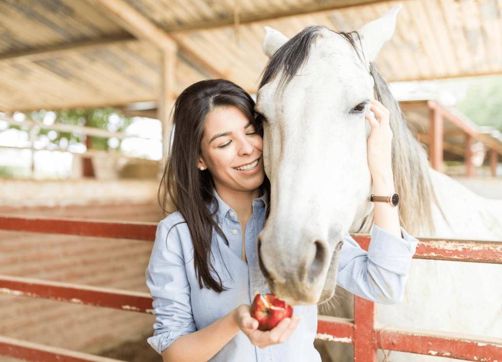 girl feeding horse with an apple